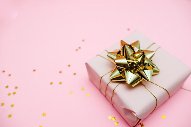 Подарочная коробка с золотым бантом на розовом фоне с отделкой и блестками.