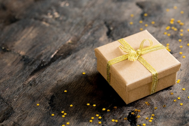 Gift box with golden bow on wooden table