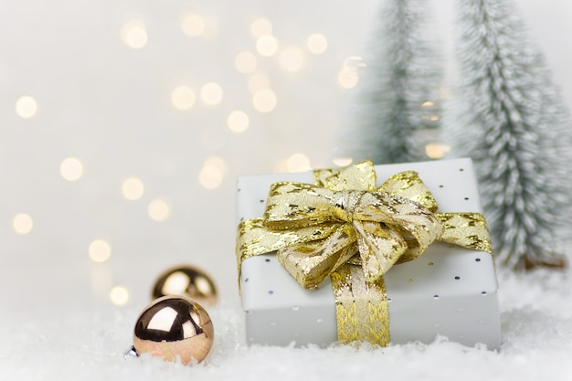 Gift box with golden ribbon bow baubles in winter forest with fir trees snow