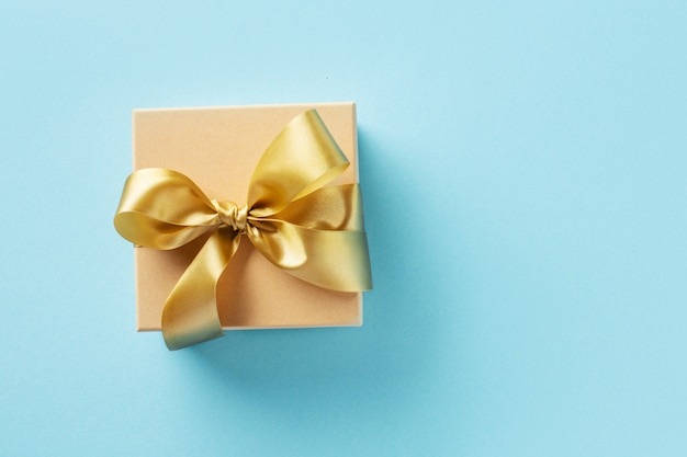 Gift box with golden ribbon on bright background