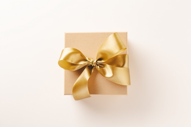 Gift box with golden ribbon on bright