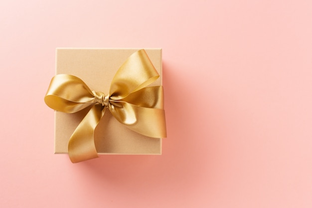 Gift box with golden ribbon on pink