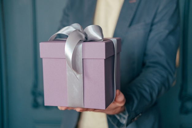 Gift box with gray silver ribbon in the hands of an elegant man on a blue background