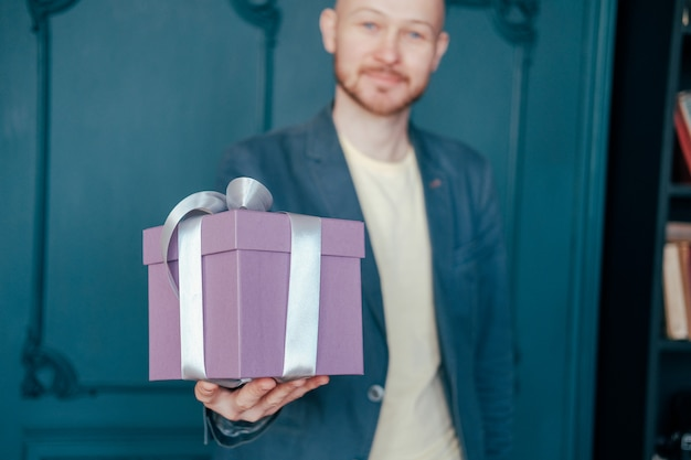 Gift box with gray silver ribbon in the hands of young attracrive man on blue background