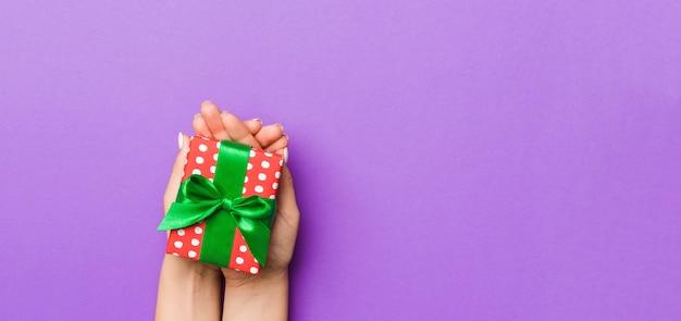 Gift box with green ribbon on purple. flat lay