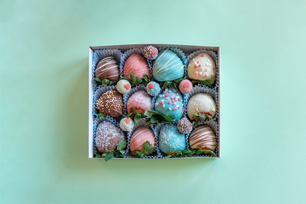 Gift box with handmade strawberry in chocolate on green background with free space for text