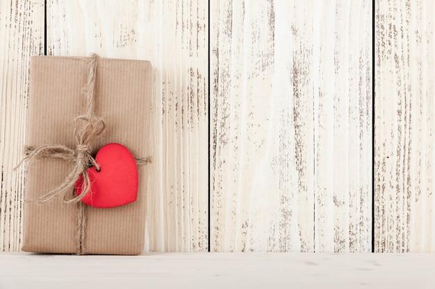 나무 배경에 하트 모양의 태그가 있는 선물 상자