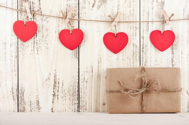 빈티지 나무 배경에 하트 모양의 태그가 있는 선물 상자