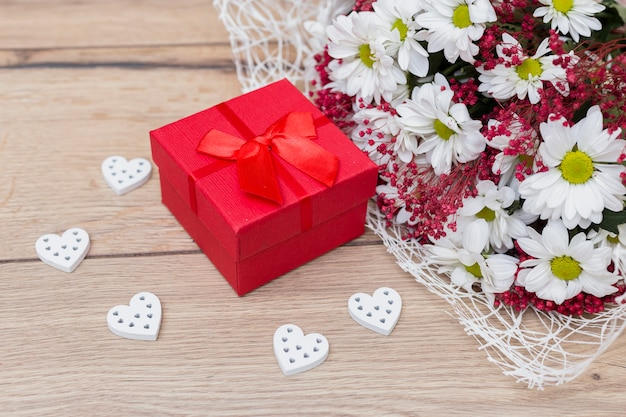 Gift box with hearts and flowers bouquet on table