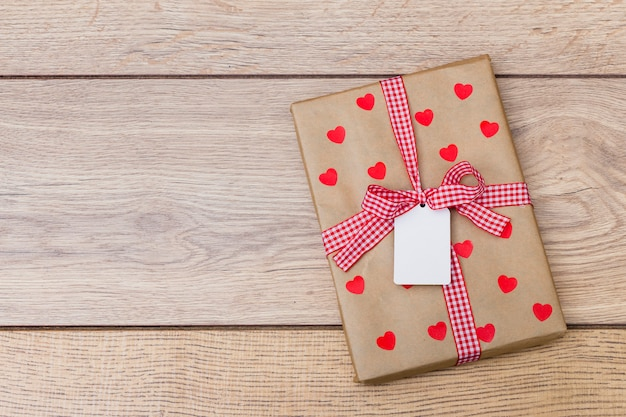 Gift box with hearts on wooden table