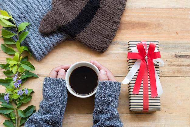 編みウールスカーフ、帽子、女性の手とギフトボックス