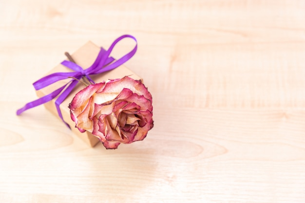 Gift box with a lilac ribbon and a bow on a wooden.
