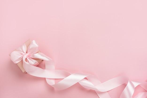 Подарочная коробка с длинной лентой на пастельно-розовом фоне. подарок на день святого валентина