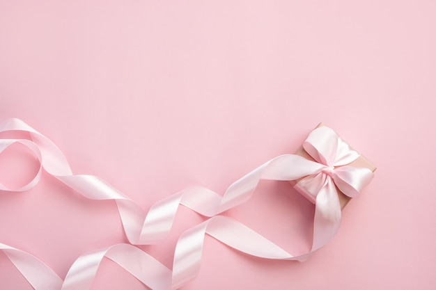 Gift box with long ribbon on pastel pink background. present for valentines day,