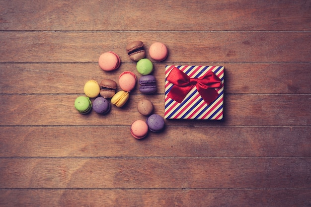 Gift box with macarons on wooden background