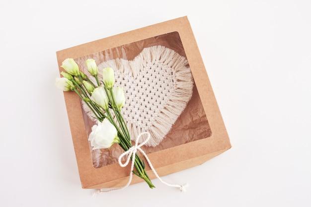 흰색 표면에 마크라메 장식 된 선물 상자. 천연 소재, 면사. 에코 장식, 장식품, 손으로 만든 장식. 심장-휴가의 상징.