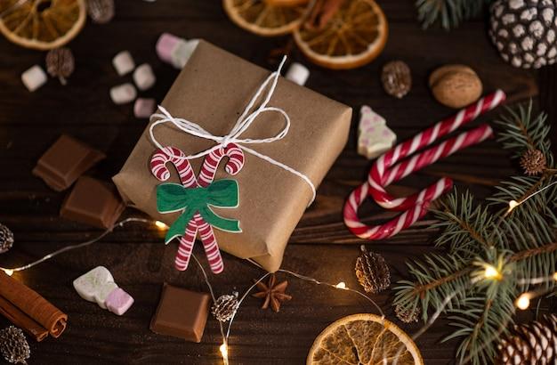 Подарочная коробка с зефиром, конфетами, корицей, шишками и шоколадом на коричневом деревянном столе, вид сверху