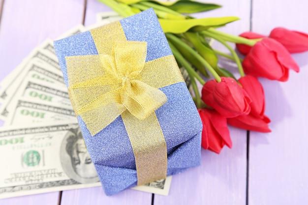 Подарочная коробка с деньгами и цветами на цветном деревянном столе
