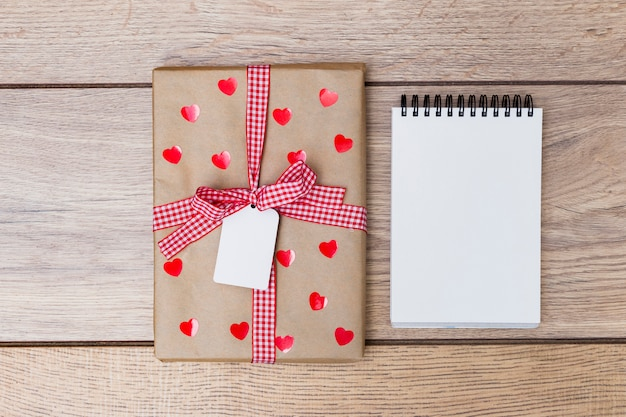 Gift box with notepad on table