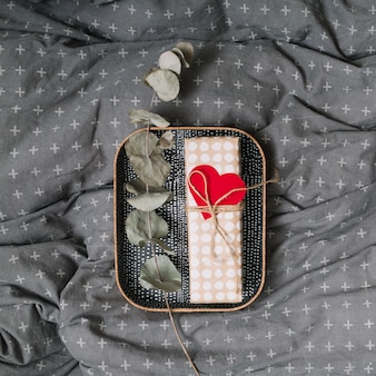 Gift box with ornament heart and plant twig on tray