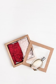 Gift box with perfume, female lace underwear red and pink colored. valentines day concept. vertical format image with copy space. top view. flat lay.