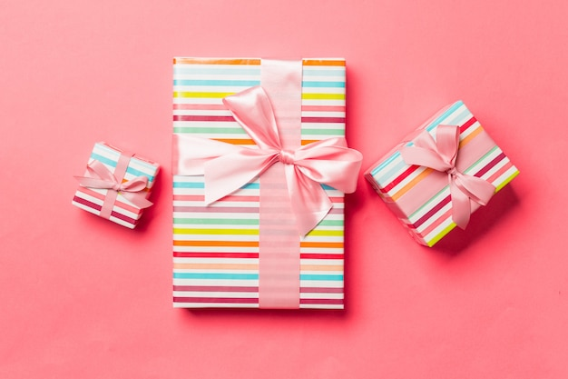 Gift box with pink bow for christmas or new year day on living coral background