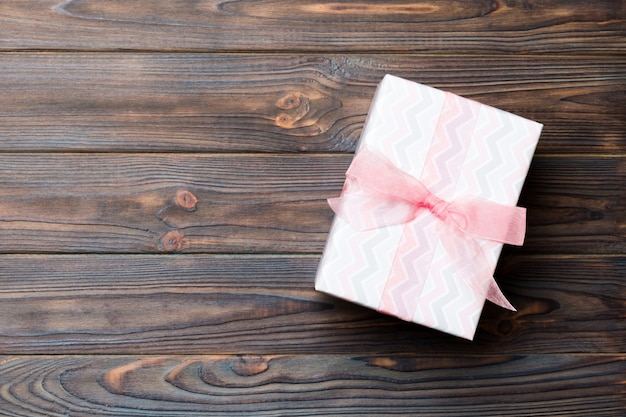 어두운 나무 테이블에 분홍색 나비 선물 상자