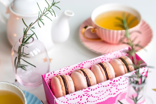Gift box with pink macaroons among vintage cups of green tea, stars and small vases