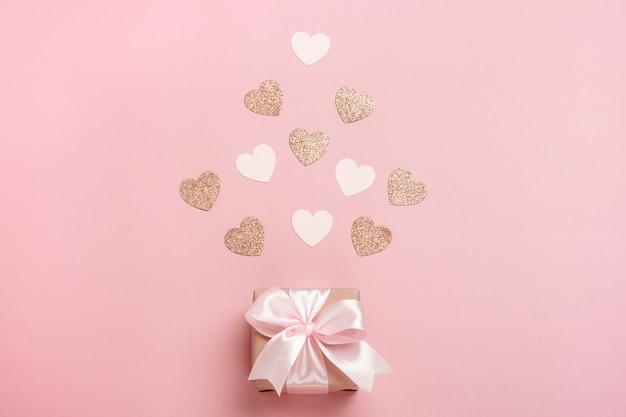 Подарочная коробка с розовой лентой на пастельно-розовом фоне с множеством сердечек.