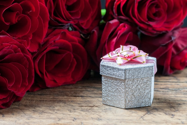 Gift box with pink ribbon and red roses behind it at grunge wooden background