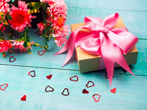 Gift box with pink satin ribbon on blue background