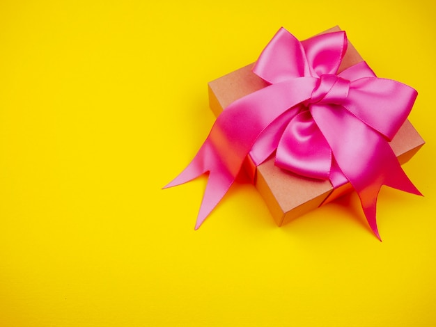 Gift box with pink satin ribbon on yellow background