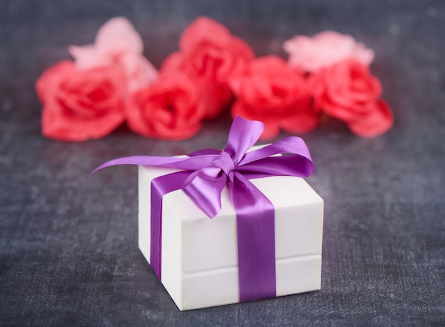 Gift box with purple ribbon and roses on gray background close up