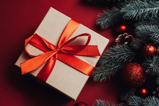붉은 나비와 빨간색 배경에 크리스마스 트리 나뭇 가지 선물 상자.