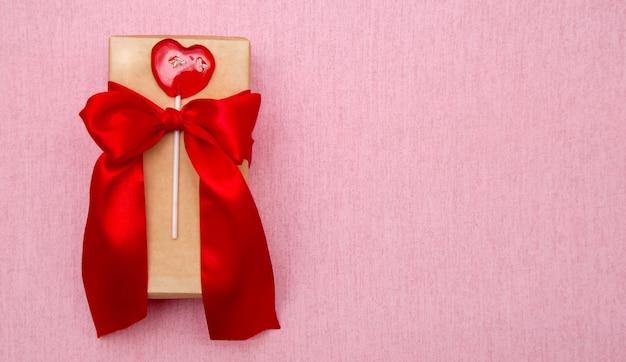 ピンクの背景に赤い弓とロリポップハートのギフトボックス。スペースをコピーします。バナー