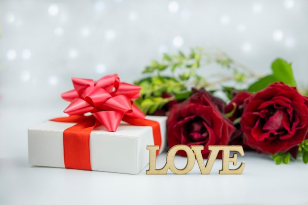 Gift box with a red bow on a background of flowers roses and bokeh with the text wooden letters love for the holiday valentine's da