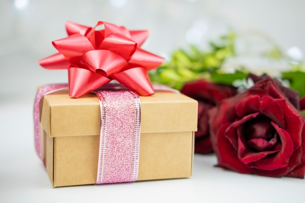 Gift box with a red bow on a background of flowers roses for the holiday valentine's da