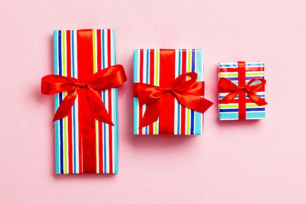 Gift box with red bow for christmas or new year day on pink background, top view