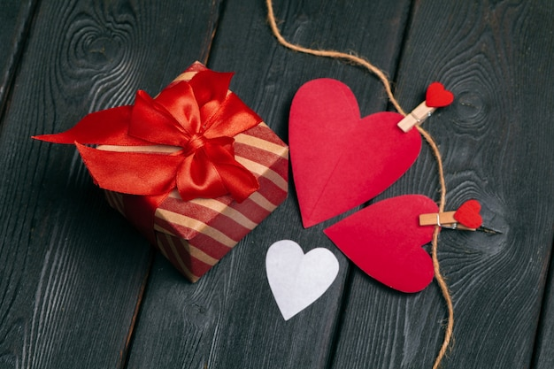 Gift box with red bow ribbon and  paper hearts for valentines day