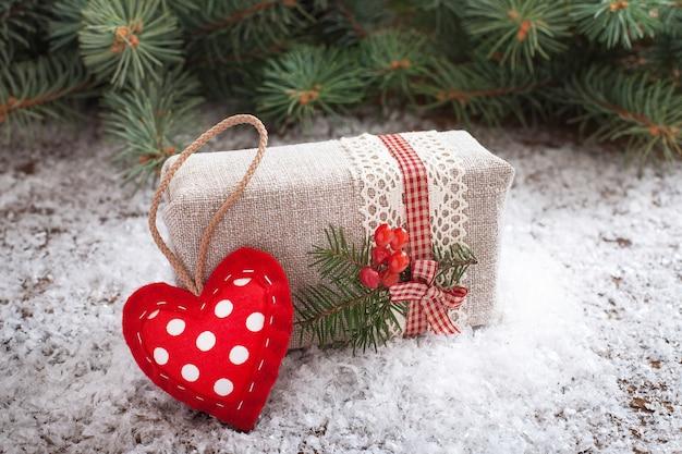 赤いハートと木製の机の上の雪のギフトボックス。セレクティブフォーカス。