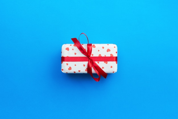 Gift box with red hearts on blue