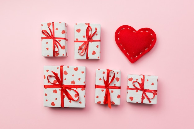Gift box with red hearts on coral background. top view with copy space