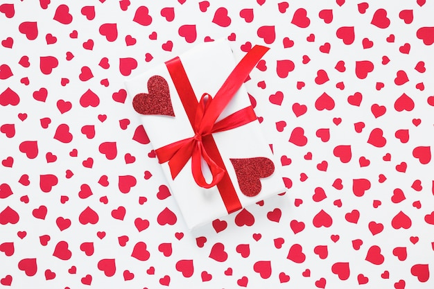 Gift box with red hearts on table