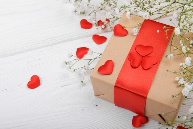 Gift box with red hearts on a white backround with small white flowers, celebration valentine's day