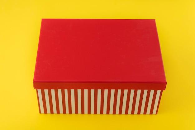黄色の背景に赤いふた付きのギフトボックス。スペースをコピーします。モックアップ。