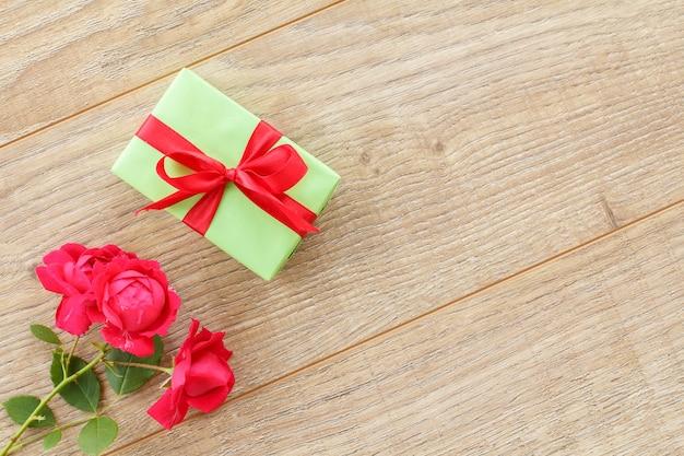赤いリボンと木製の背景に美しいバラの花のギフトボックス。休日に贈り物をするという概念。上面図。