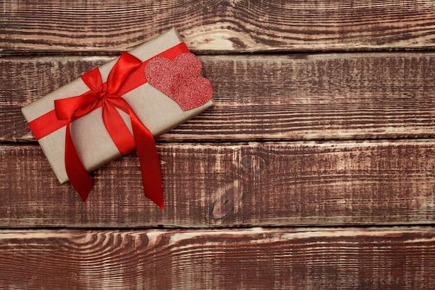 木製の背景に赤いリボンとハートのギフトボックス。ソフトセレクティブフォーカス。スペースをコピーします。