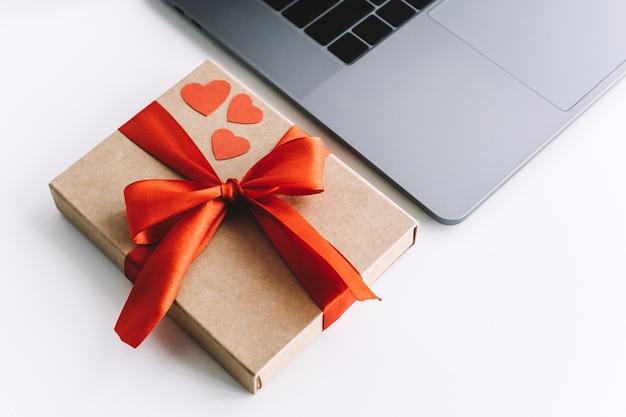 Подарочная коробка с красной лентой и сердечками на столе возле ноутбука. концепция сюрприза на день святого валентина