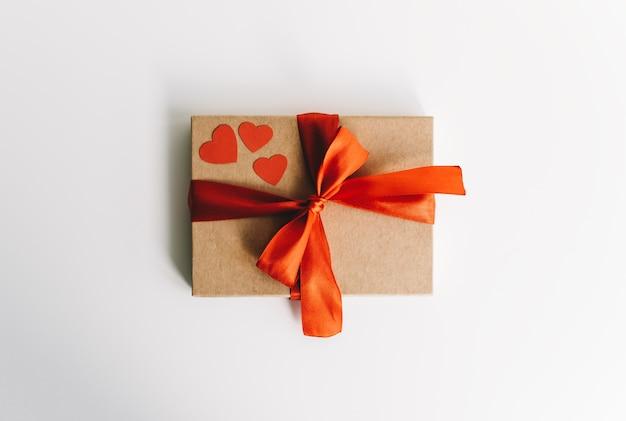 Подарочная коробка с красной лентой и сердечками на белом столе. концепция сюрприза на день святого валентина