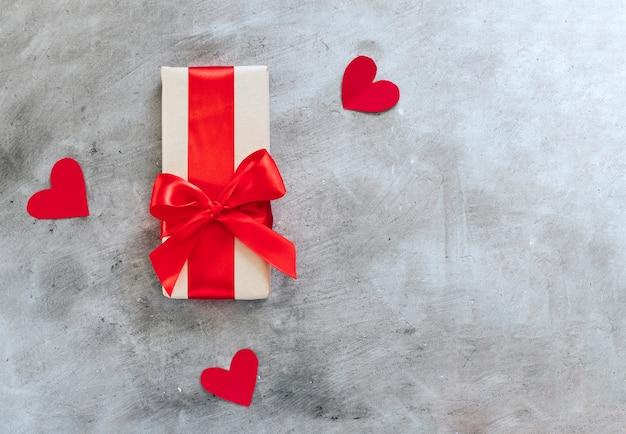 Подарочная коробка с красной лентой и сердечками.